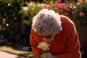 senior woman sniffing flower